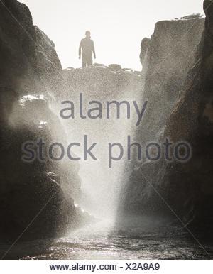 Silhouette eines Mannes stehen auf Felsen durch Gezeiten Ozeanbecken - Stockfoto
