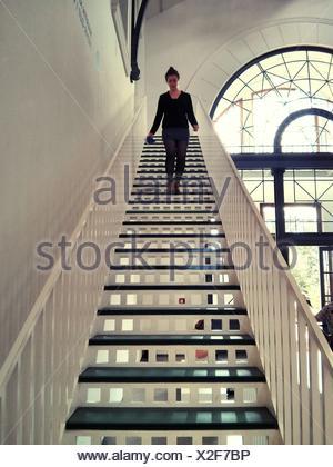 Junge Frau, die Treppe hinunter zu Hause bewegen - Stockfoto