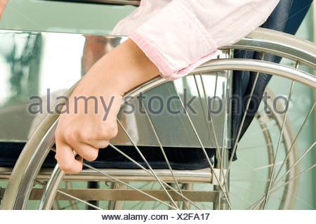 Eine Frau in einem Rollstuhl sitzt - Stockfoto