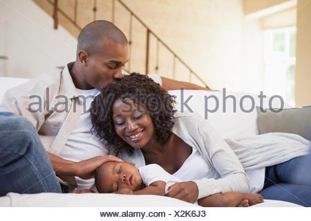 Babyjungen schlafen friedlich auf Couch mit glücklichen Eltern - Stockfoto