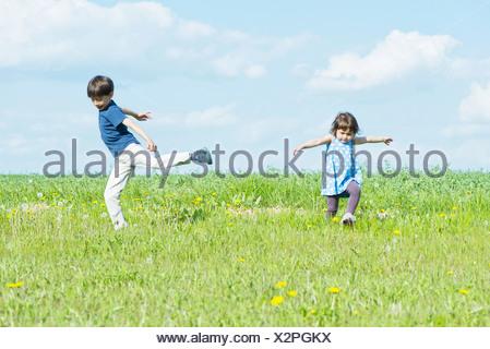 Kinder laufen im Feld mit Armen - Stockfoto