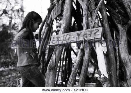 Mädchen in der Nähe von Haufen von Holz Stockfoto