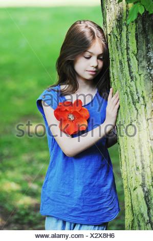 Mädchen lehnte sich gegen Baum im park - Stockfoto