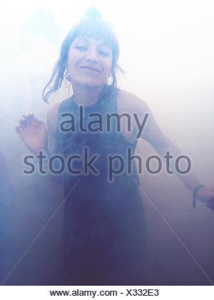 Porträt von glücklich Frau tanzt im Rauch Stockfoto