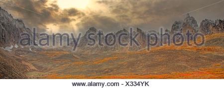 Clearing-Sturm, Strahlen der Sonne durch die Wolken und Herbstfarben im Tombstone Tal in Tombstone Territorial Park, Yukon stossen - Stockfoto