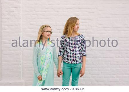 Zwei Schwestern Hand in Hand neben weißen Wand - Stockfoto