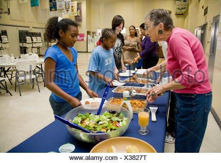 Selena Pina, eine Obdachlose Mutter von vier und ihre Kinder stehen Schlange, Abendessen, zubereitet von Freiwilligen der Familie versprechen erhalten