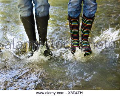 Glückliches Paar tragen bunte Regen Stiefel - Stockfoto