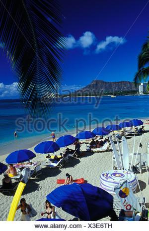 Urlauber genießen Sie einen Blick auf den Diamond Head Krater wie entspannen sie auf warmen, einladenden Sandstrand von Waikiki Beach. Dieses Foto - Stockfoto