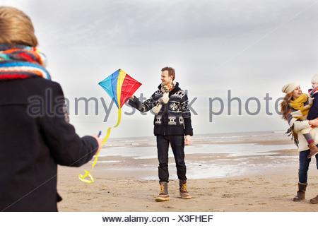 Mitte Erwachsenen Eltern mit Sohn und Tochter spielen mit Kite am Strand von Bloemendaal Aan Zee, Niederlande - Stockfoto