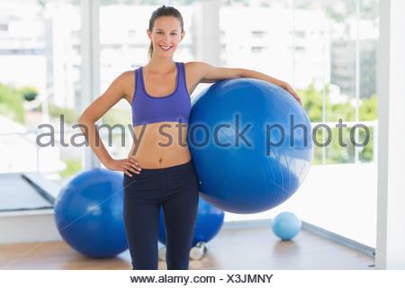 Lächelnde Frau hält Fitnessball in Turnhalle passen - Stockfoto