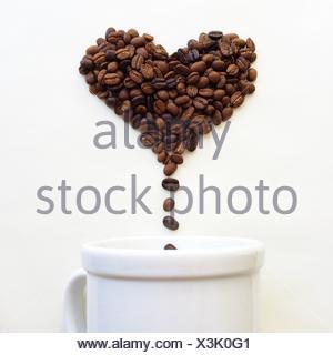 Kaffeebohnen in Form von Herzen fallen in eine Kaffeetasse Stockfoto