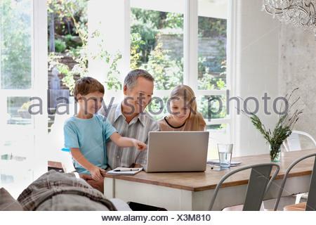 Familie mit Laptop zusammen am Esstisch - Stockfoto