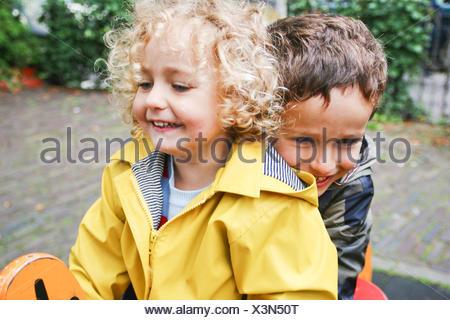 Lächelnden jungen und Mädchen sitzen auf Frühling reiten auf Spielplatz - Stockfoto