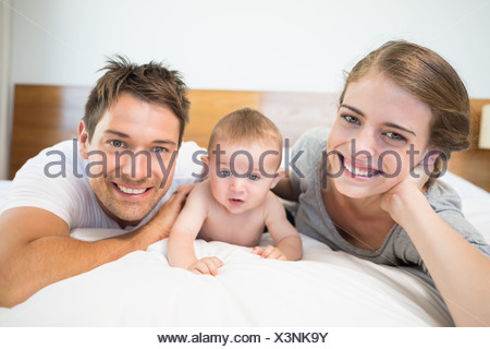 Glückliche Eltern mit Baby Sohn auf Bett liegend - Stockfoto