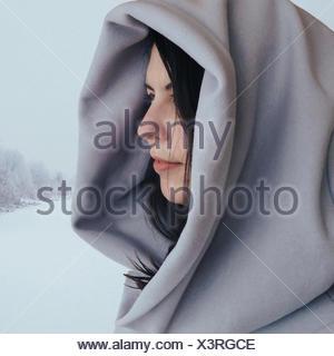 Porträt einer Frau, die im Schnee mit einem Kapuzenmantel steht, Calgary, Alberta, Kanada - Stockfoto