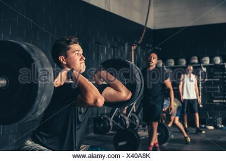 Mann und Trainer Ausbildung mit Langhantel in Turnhalle - Stockfoto