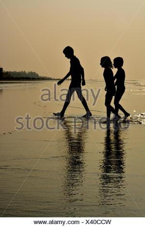 Silhouette von drei Kindern, die zu Fuß aus dem Meer, Madarmoni Strand, Digha, Indien - Stockfoto