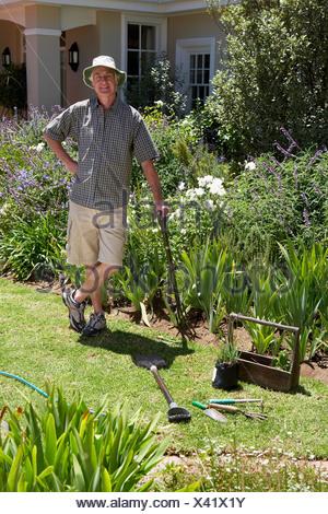 Ältere Mann auf Rasen Gartenarbeit stützte sich auf Garten Gabel Hand auf Hüfte, Lächeln, Porträt - Stockfoto