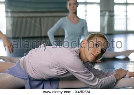 Weiblichen Balletttänzer stretching-Übungen auf dem Boden zu tun Stockfoto