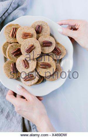 Eine Frau, ein Teller voller Pecan Spritzgebäck ist aus der Draufsicht fotografiert. - Stockfoto