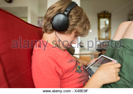 Junge Musik über Kopfhörer hören und mit digital-Tablette - Stockfoto