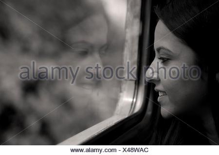Frau sitzt in einem Zug, der Blick aus dem Fenster - Stockfoto