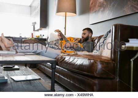 Mann spielt Gitarre auf Sofa im Wohnzimmer - Stockfoto