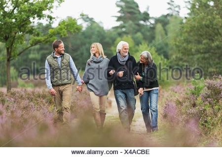 Zwei Paare, die zu Fuß durch Wald - Stockfoto