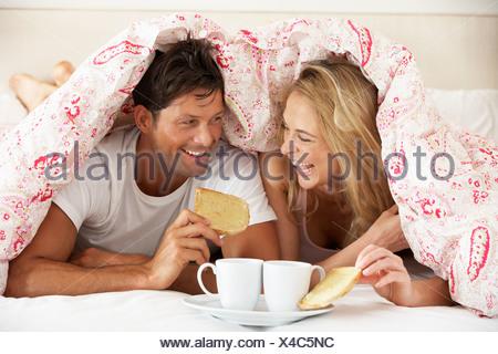 Paar kuschelte sich unter die Bettdecke zu frühstücken