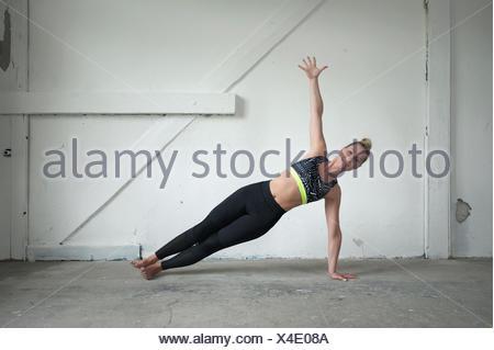 Mitte Erwachsene Frau üben Seite Plank Pose im Yoga-Studio, München, Bayern, Deutschland - Stockfoto