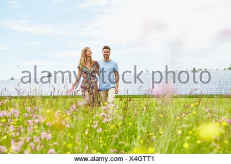 Junges Paar Spaziergang durch Feld neben Solarpark - Stockfoto