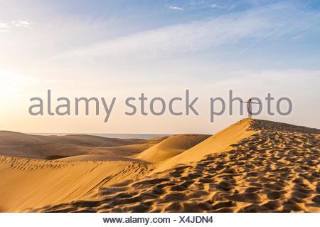 Frau auf Sanddüne mit ausgestreckten Armen - Stockfoto