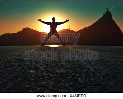 Silhouette des Mannes Flickschusterei am Strand bei Sonnenuntergang, Rio De Janeiro, Brasilien - Stockfoto