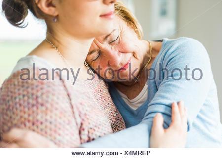 Ältere Frau mit geschlossenen Augen, die junge Frau Schulter gelehnt