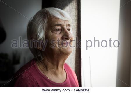 Ältere Frau stehen in der Nähe von Fenster - Stockfoto