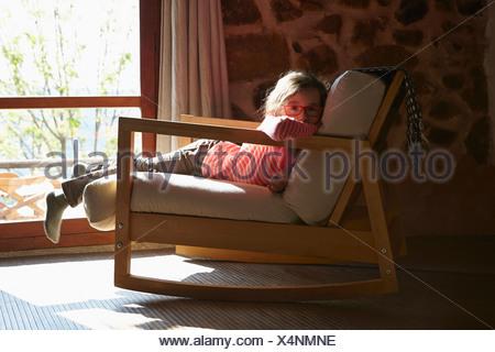 Porträt des jungen Mädchens auf Schaukelstuhl liegend - Stockfoto