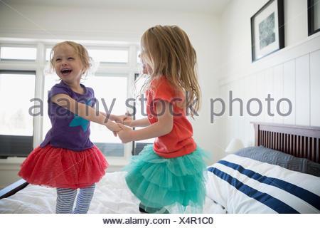 Verspielte Schwestern Hand in Hand und springen auf Bett - Stockfoto