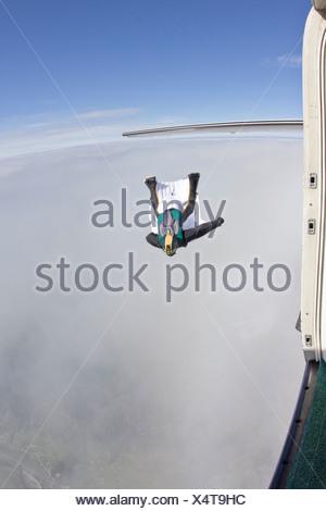 Mitte erwachsenen Mannes über Wolken im Wingsuit fliegen