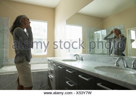 Frau nachdenklich vor Spiegel - Stockfoto