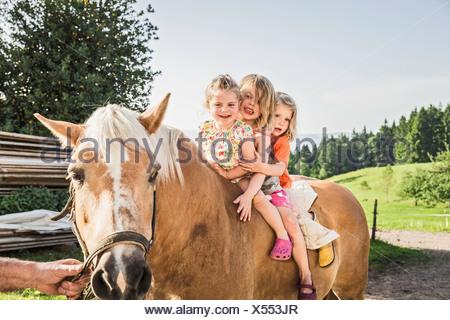 Drei junge Mädchen sitzen auf Palomino Pferd - Stockfoto