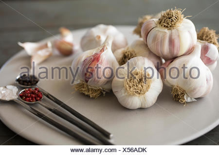 Teller mit Knoblauch Blubs mit Steinsalz Himalaya Pink und rosa und schwarze Pfefferkörner. - Stockfoto