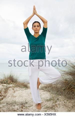 Reife Frau in Baumpose am Strand, Porträt