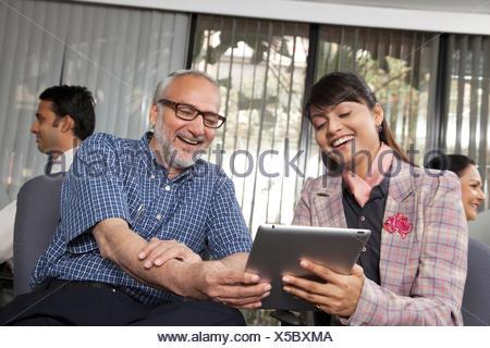 Ältere Mann und Frau betrachten eine Tablette - Stockfoto