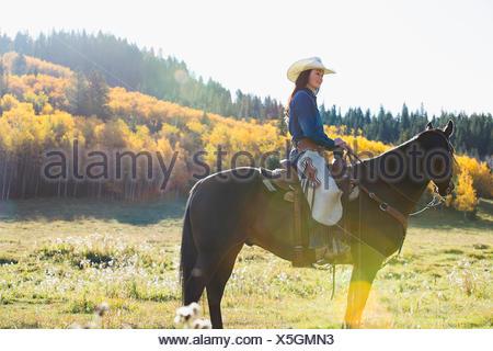 Frau sitzend Reiten im sonnigen herbstlichen Feld - Stockfoto