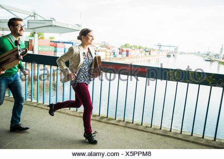 Junge Frau und Mann mit Skateboard auf Brücke - Stockfoto