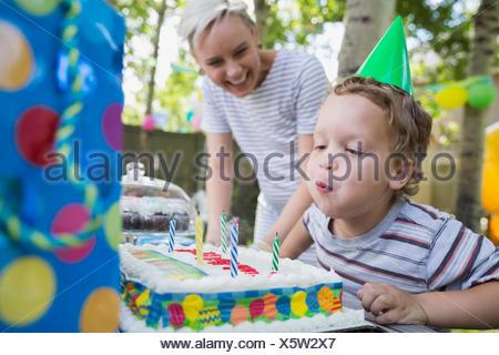 Boy bläst Geburtstagskerzen Kuchen Hinterhof - Stockfoto