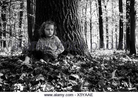 Mädchen im Wald an einen Baumstamm gelehnt sitzt - Stockfoto
