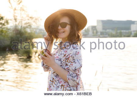 Porträt der jungen Frau, stehend neben See - Stockfoto