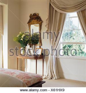 swagged und tailed cremefarbene vorh nge im wohnzimmer mit lila sofa und teppich und rot. Black Bedroom Furniture Sets. Home Design Ideas